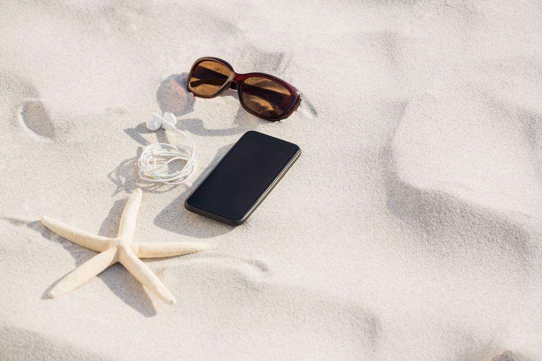 Starfish, sunglasses, headphones and mobile phone kept on sand at beach Free Stock Images from PikWizard