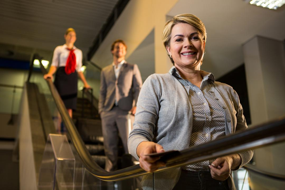 Businesswoman with boarding pass standing on escalator in airport