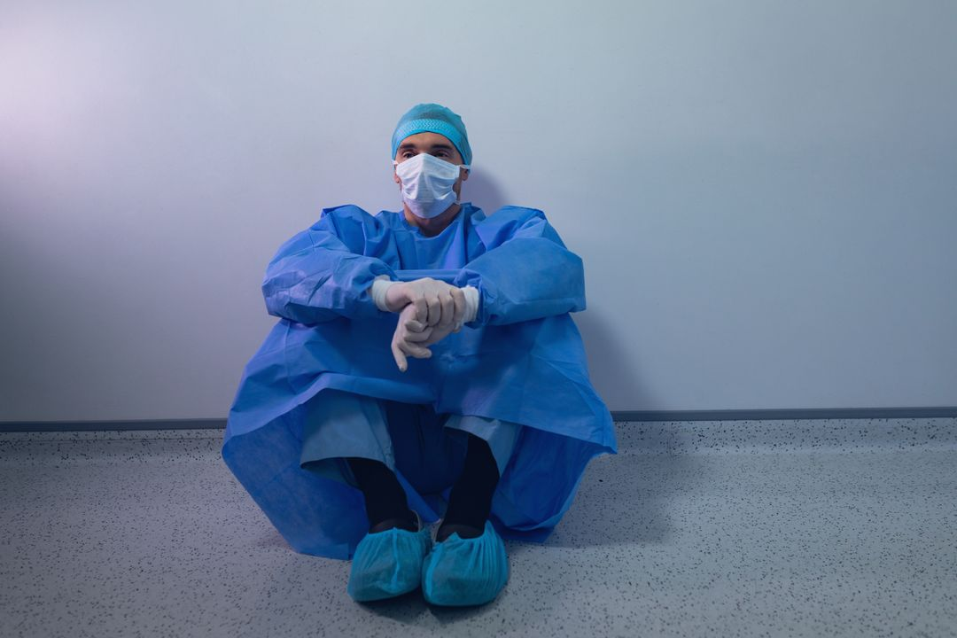 Thoughtful male surgeon sitting in operating room at hospital