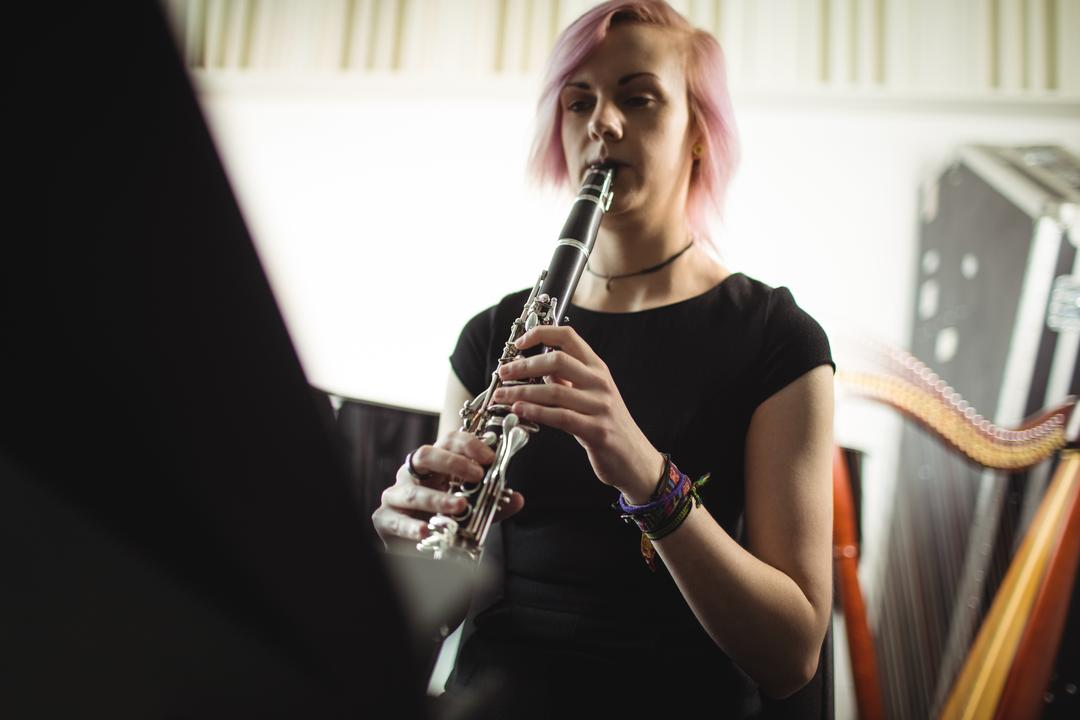 Beautiful woman playing a clarinet in music school