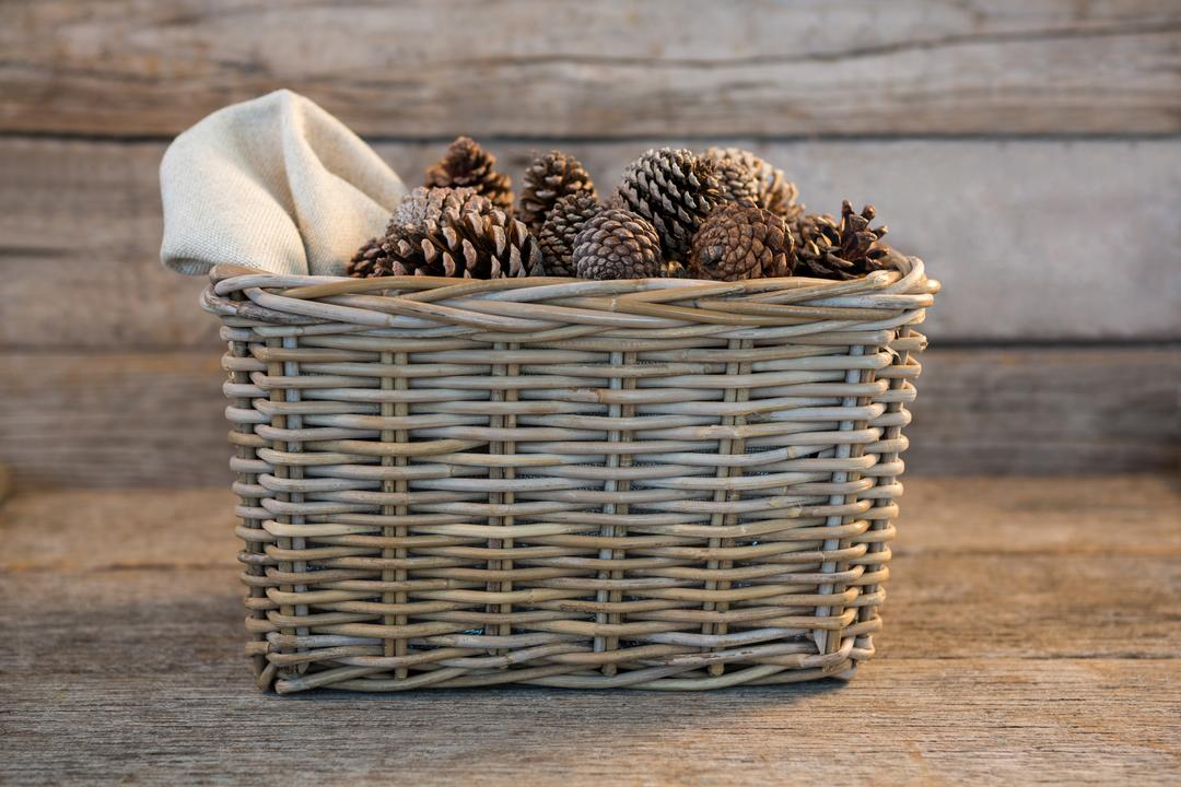 Pine cones in wicker basket on wooden plank during christmas time Free Stock Images from PikWizard