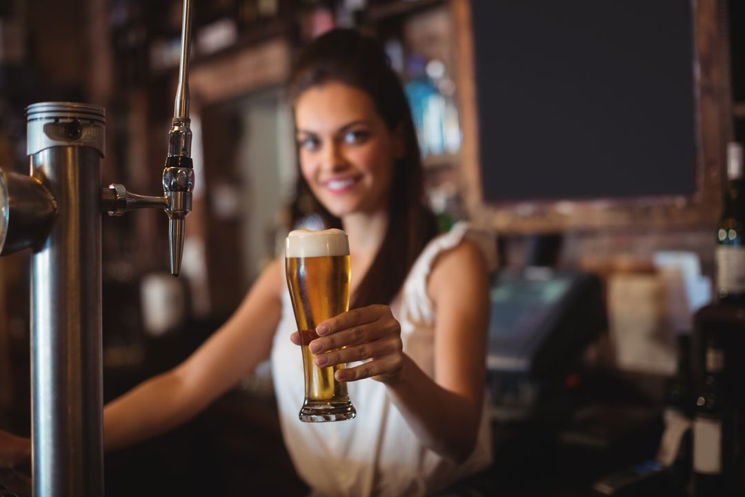 Portrait of female bar tender holding glass of beer at bar counter Free Stock Images from PikWizard