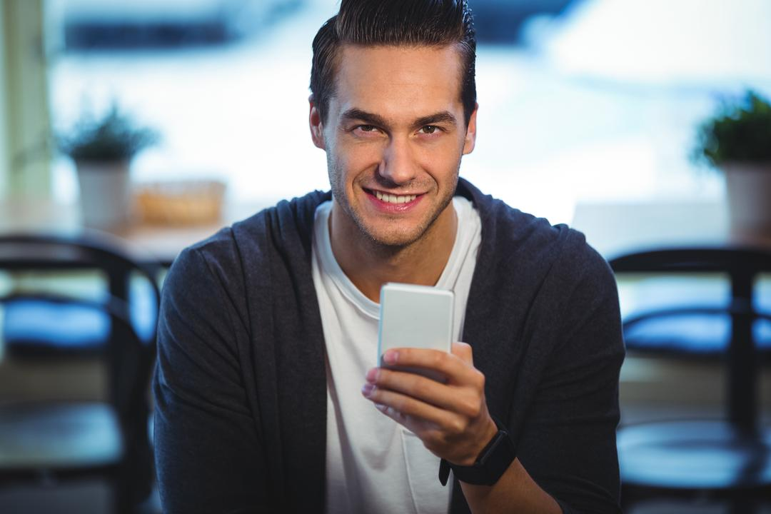 Portrait of smiling man using mobile phone in cafe