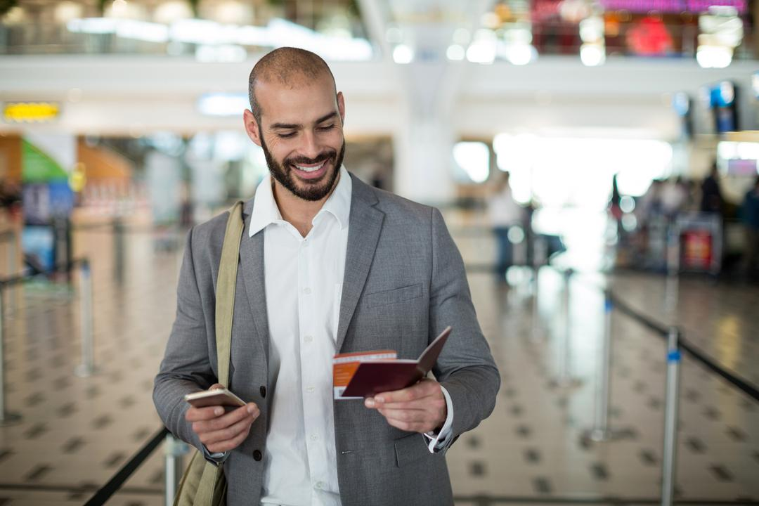 Smiling businessman holding a boarding pass and checking his mobile phone at airport terminal