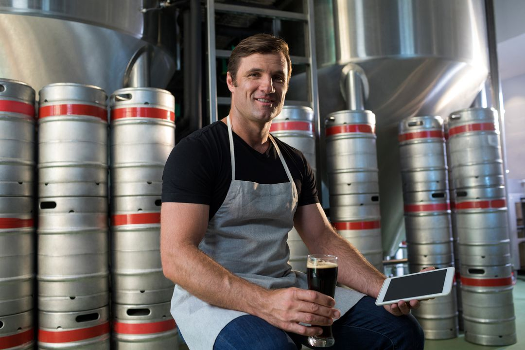 Portrait of worker holding tablet and beer while sitting by kegs at warehouse