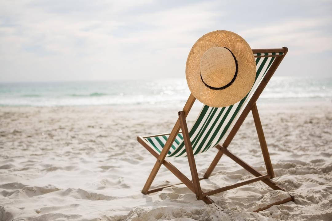 Straw hat kept on empty beach chair at tropical sand beach