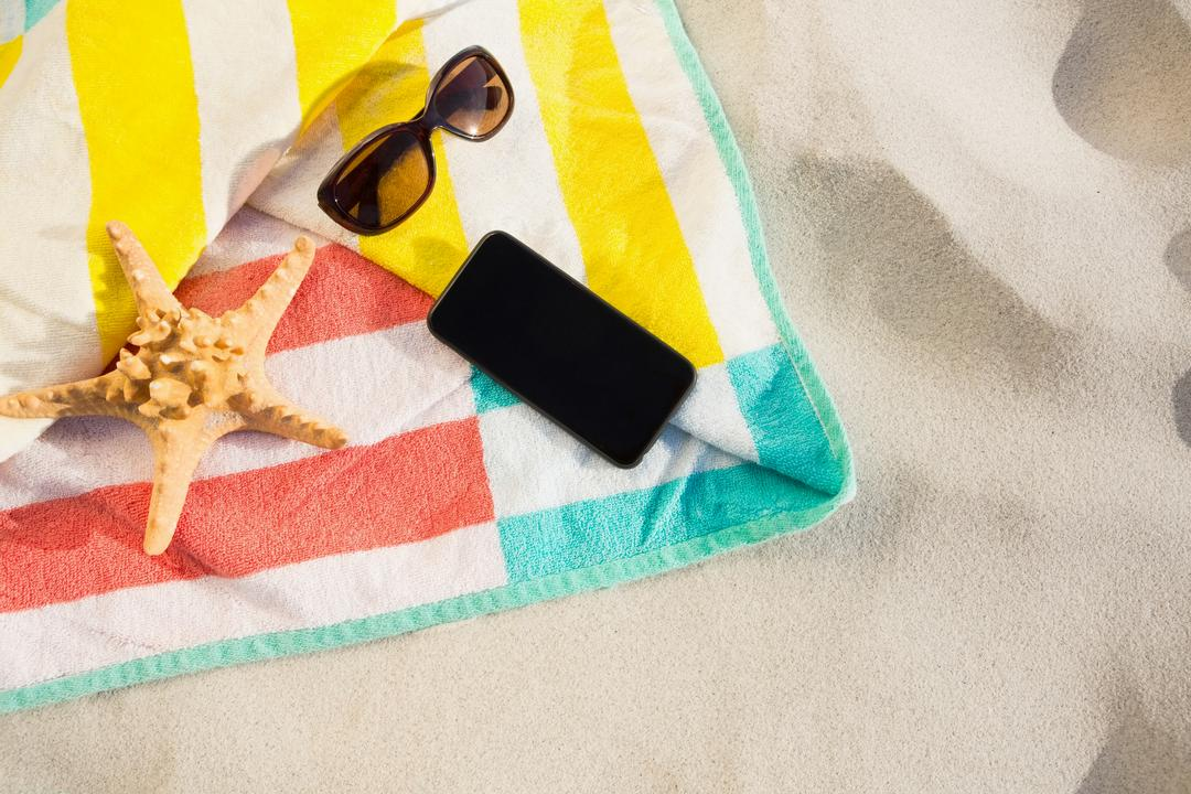 Starfish, sunglasses and mobile phone kept on beach blanket at beach