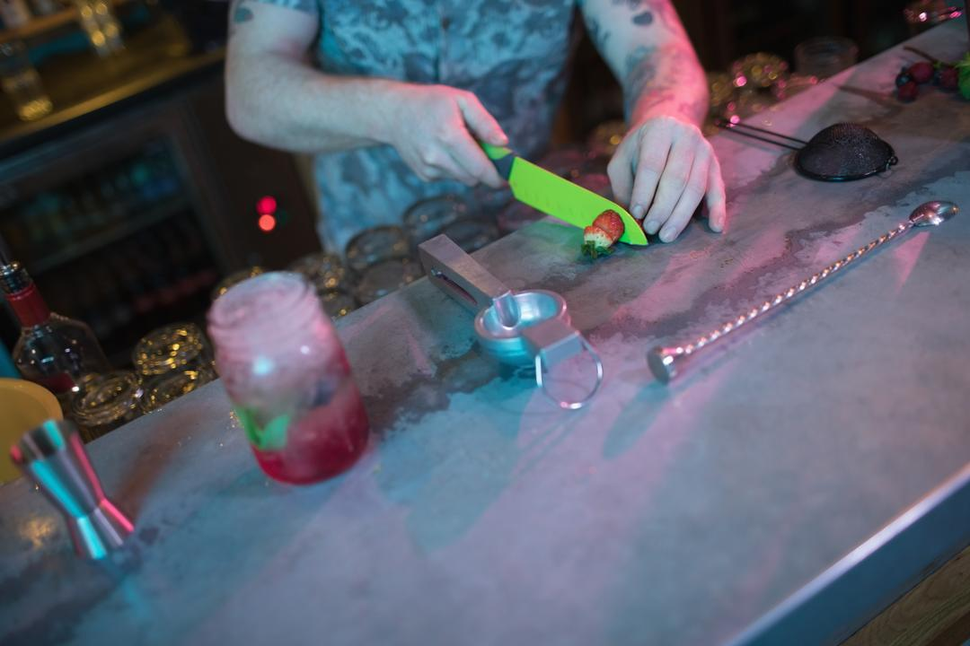 Bartender cutting strawberry for preparing cocktail at counter in bar