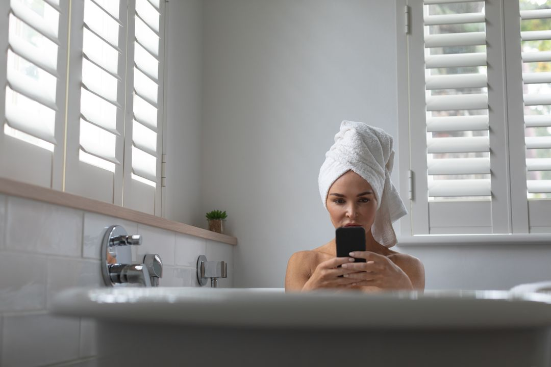 Beautiful woman using mobile phone while sitting in bathtub at home