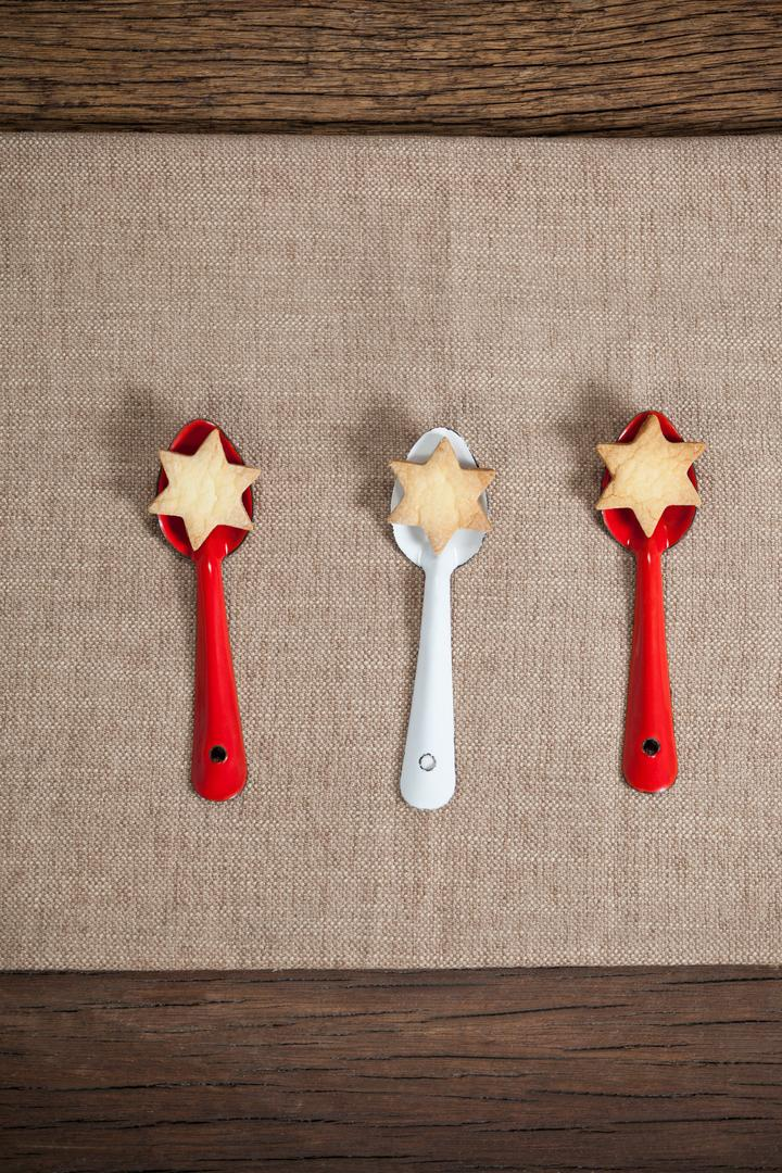 Red and white spoon with christmas cookies arranged on wooden table Free Stock Images from PikWizard