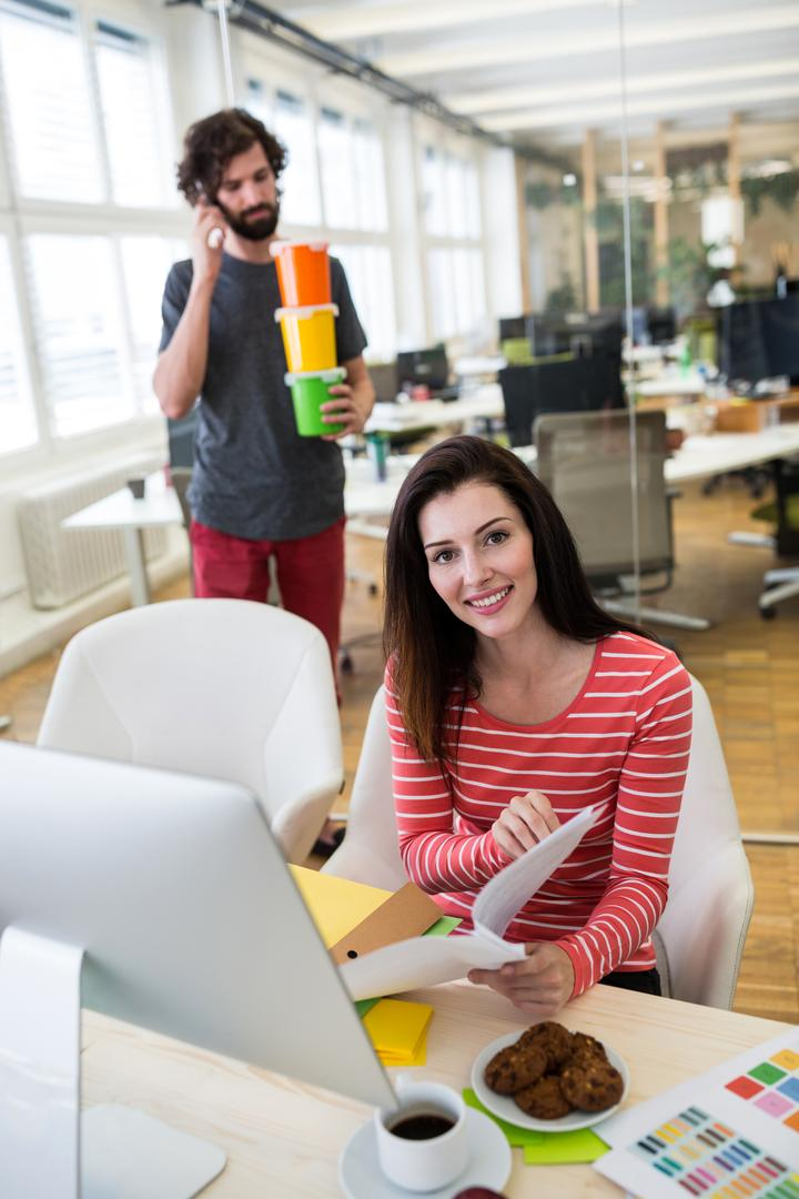 Female graphic designer working over a document while male graphic designer holding plastic container in background in office