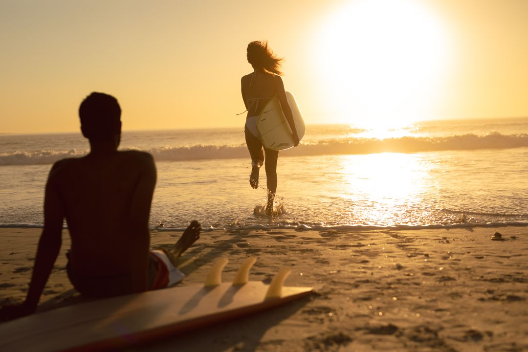 Rear view of woman running with surfboard while man relaxing on the beach during sunset