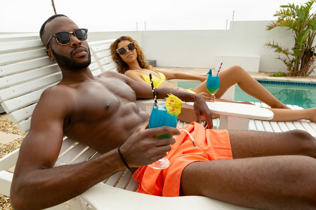 Side view of cute diverse couple having cocktail drink while relaxing on a sun lounger near swimming pool. Summer fun at home by the swimming pool Free Stock Images from PikWizard