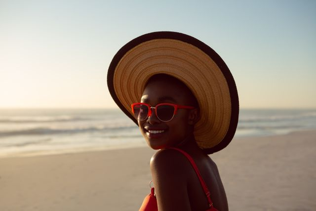Woman in hat and sunglasses relaxing on the beach