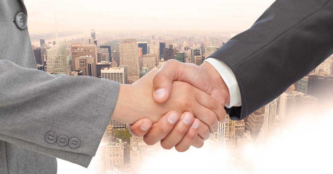 Digital composite of Close-up of handshake with buildings in background