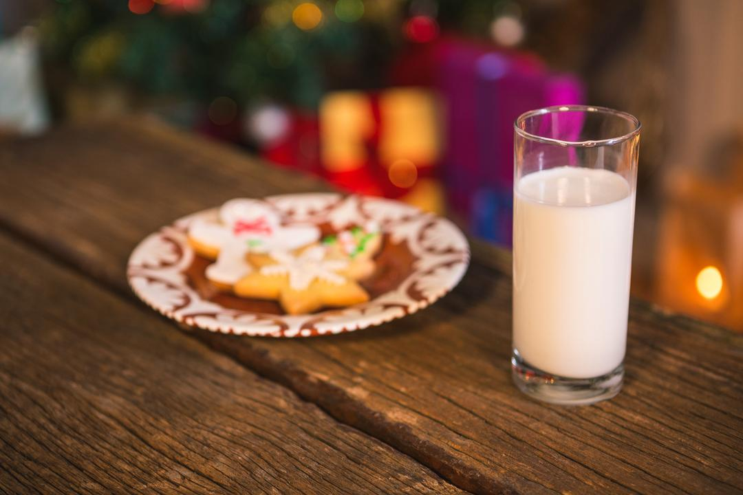 Gingerbread cookies with a glass of milk on wooden table during christmas time