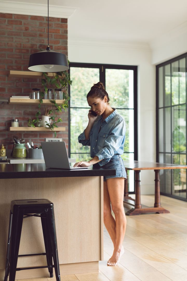 Beautiful woman talking on mobile phone while using laptop on worktop in kitchen at comfortable home