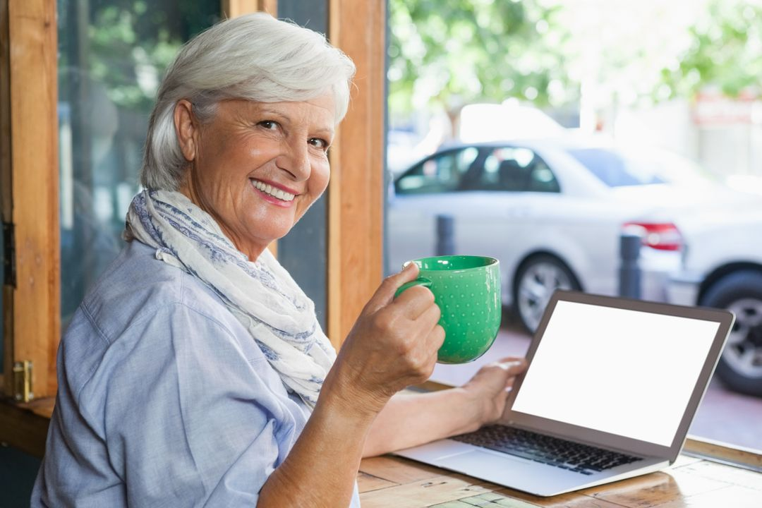 Portrait of smiling senior woman holding coffee cup while sitting at table in cafe shop Free Stock Images from PikWizard