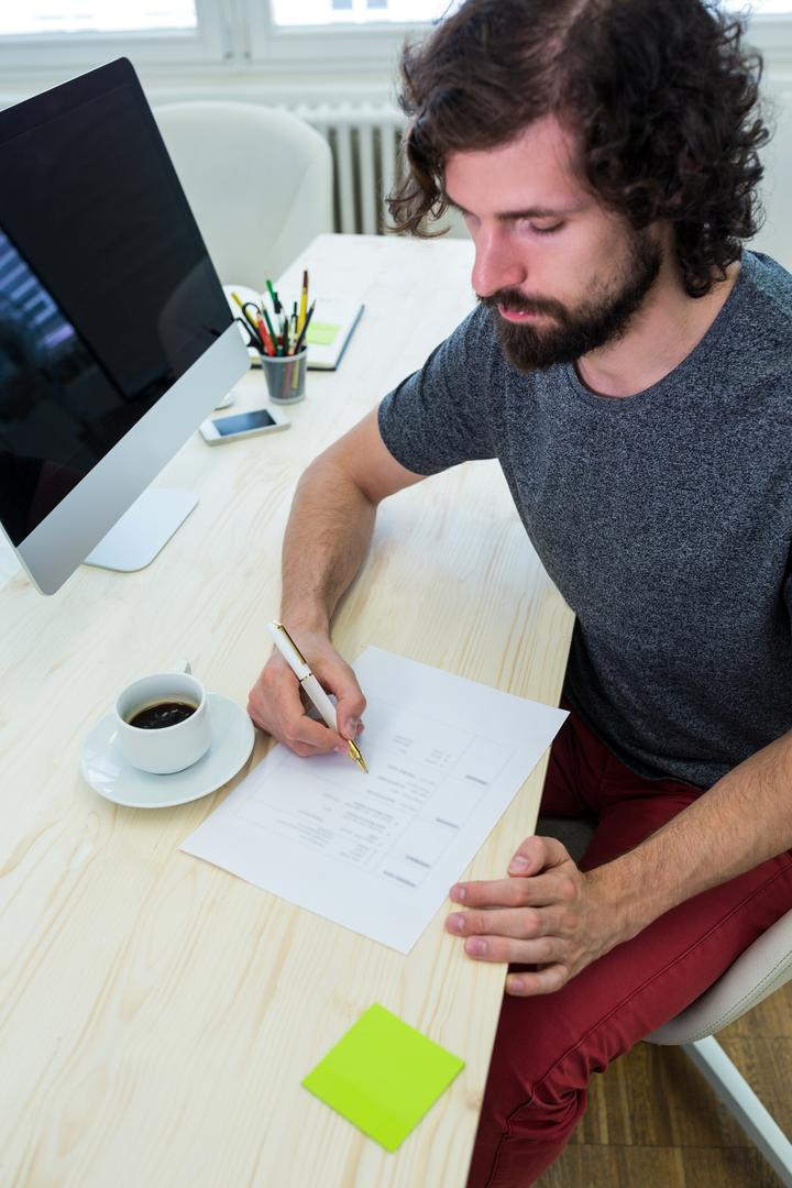Male graphic designer filling a form in office Free Stock Images from PikWizard