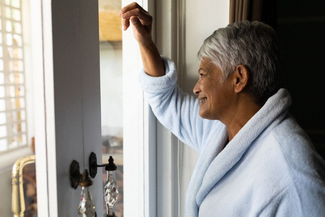 Senior african american woman standing by a window in a bedroom. Retirement lifestyle in self isolation during coronavirus covid 19 pandemic. Free Stock Images from PikWizard