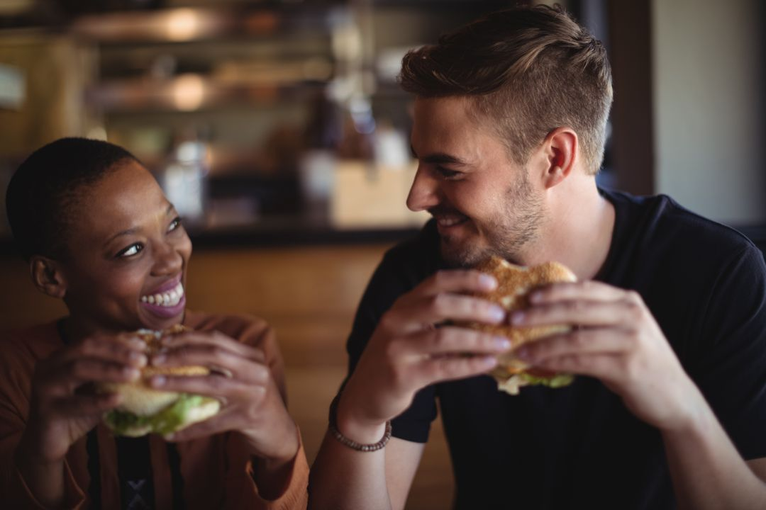 Diverse happy couple enjoying a buger