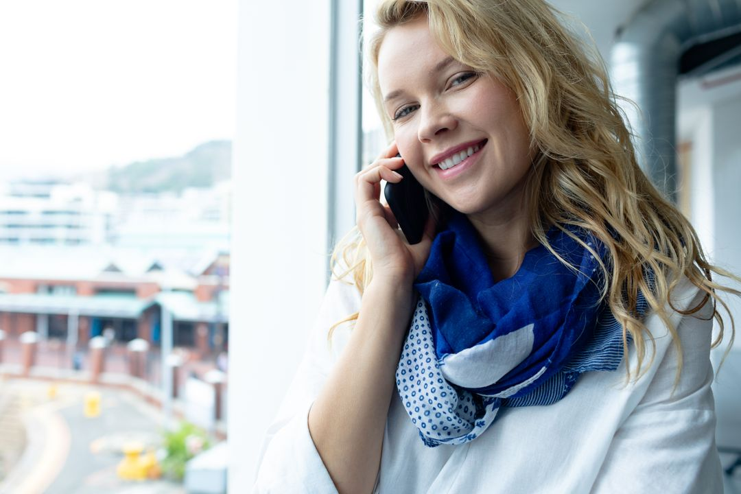 Front view of beautiful young caucasian businesswoman looking at camera while talking on mobile phone near window in a modern office