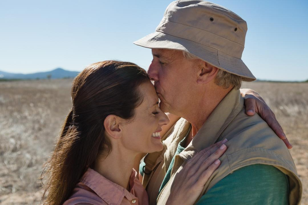 Mature man kissing woman forehead on landscape