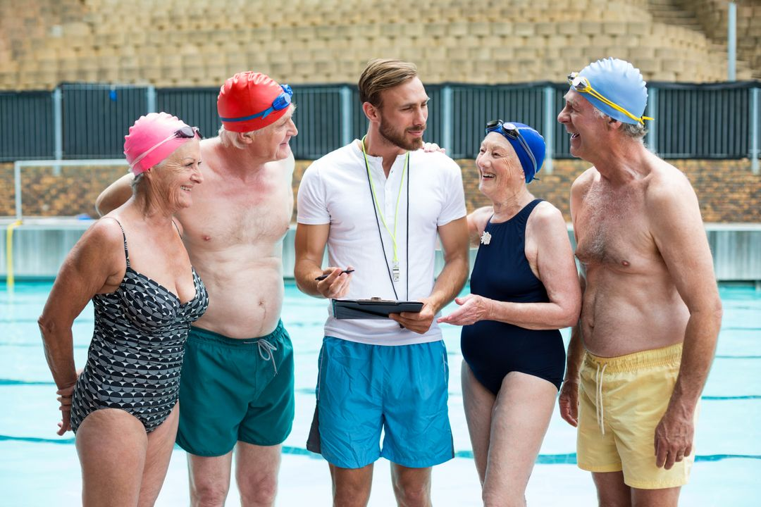 Group of seniors people with instructor standing at poolside