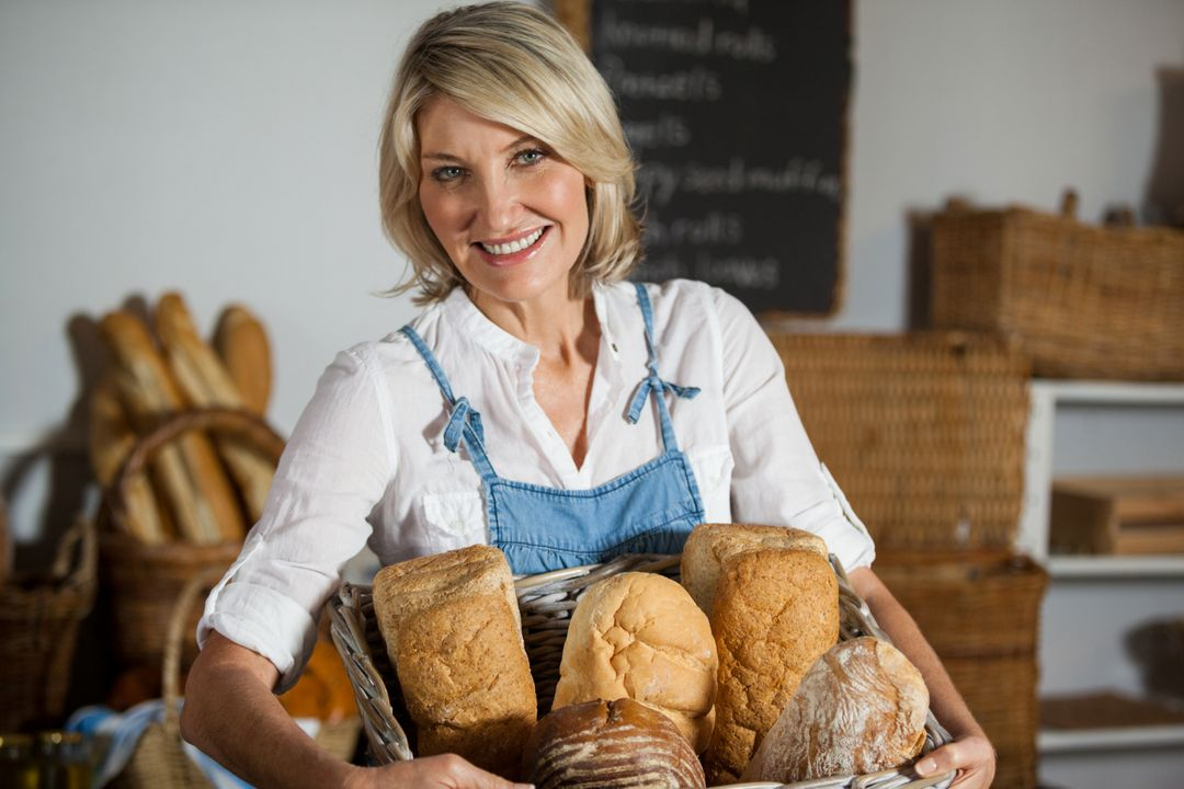 Female staff holding basket of bread in bakery section of supermarket