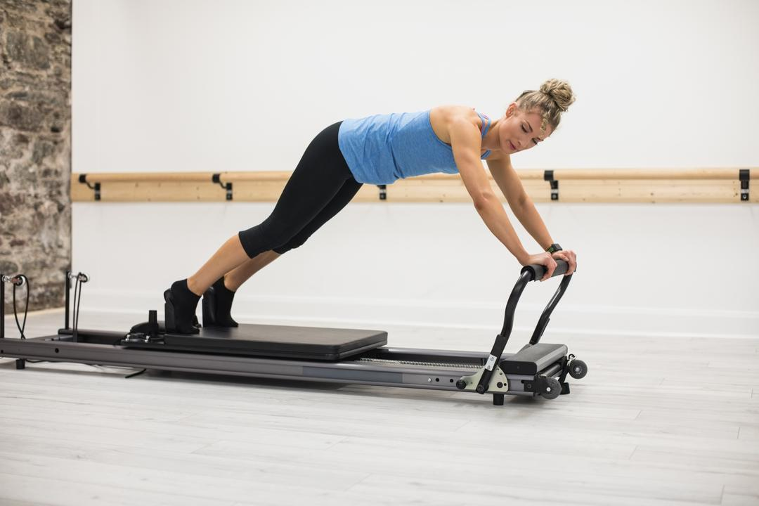 Woman exercising on reformer in gym