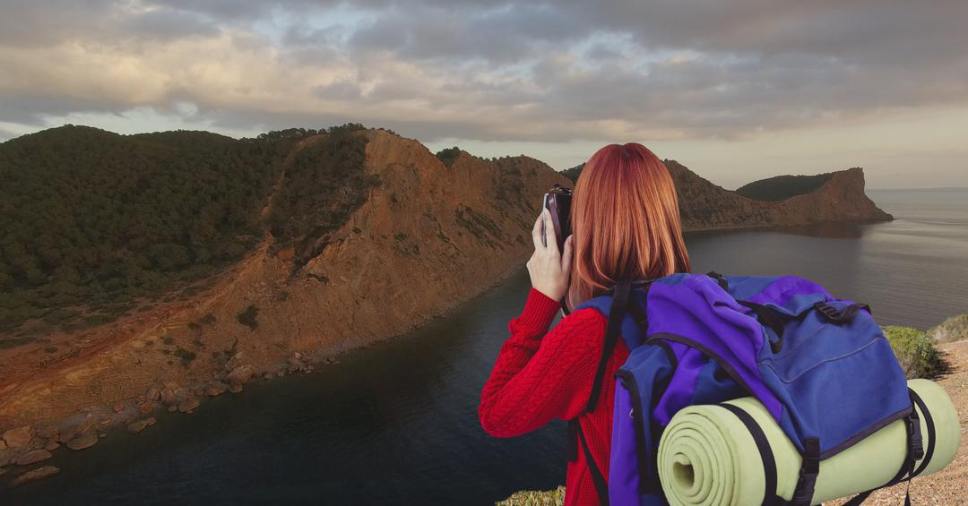 Digital composite of mountain travel, red hair woman taking a photo