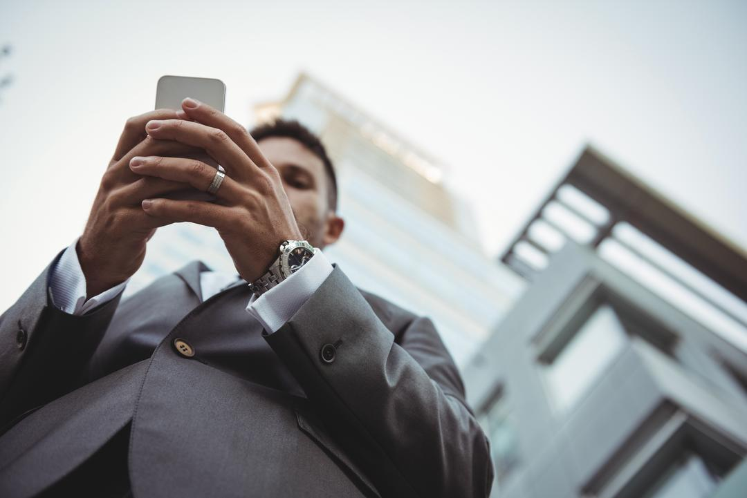 Businessman using mobile phone near office building