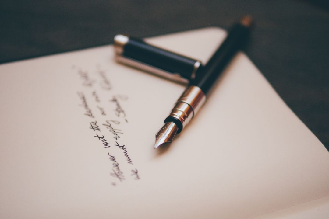 Motivational black Caligraphy pen placed over a notebook with some words written in it