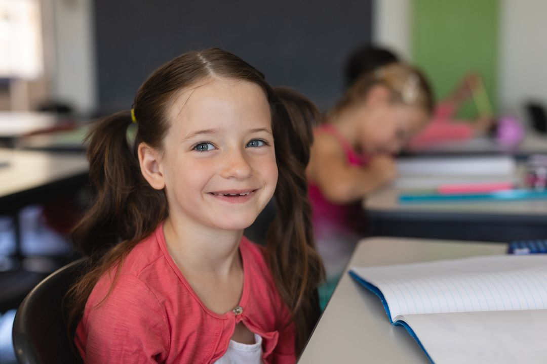Portrait of a happy schoolgirl looking at camera while sitting at desk in classroom Free Stock Images from PikWizard