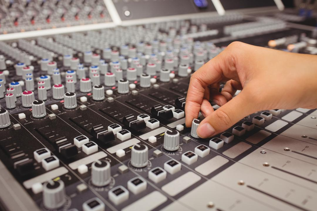 Hand of a female student using sound mixer in a studio