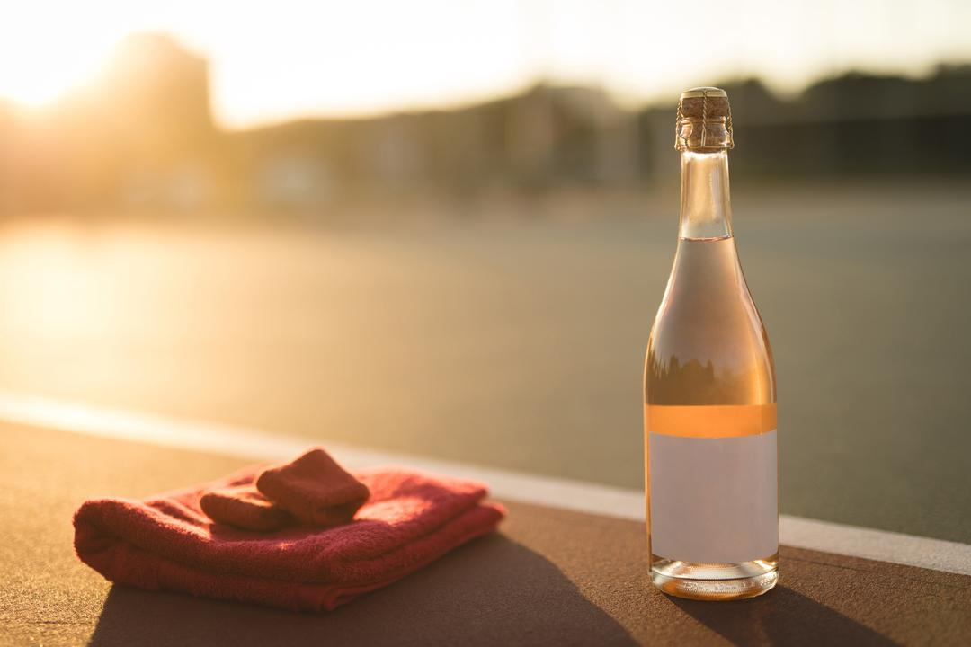 Folded napkin, wristband and bottle in ground on a sunny day Free Stock Images from PikWizard