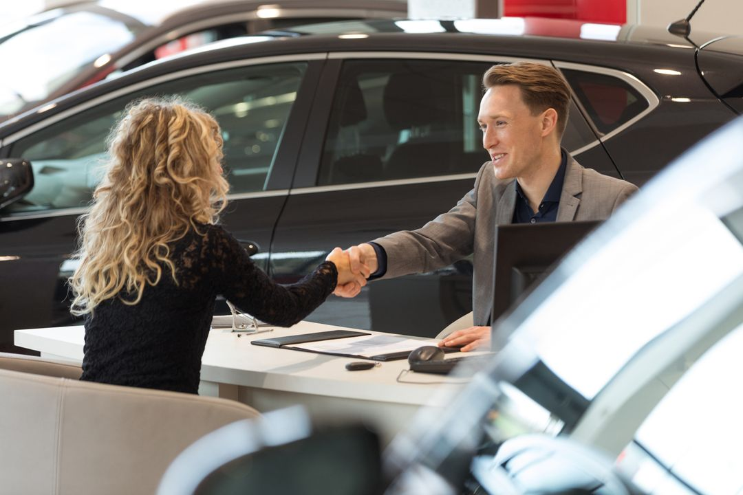 Smiling salesman doing handshake with female customer while sitting desk in car showroom