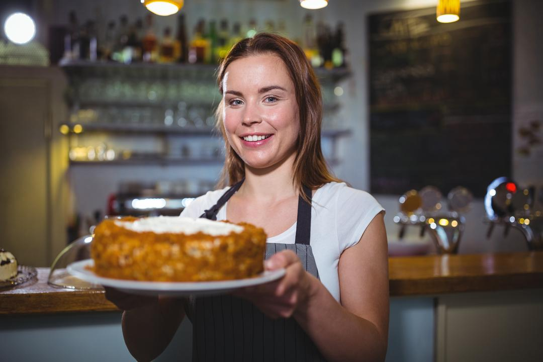 Portrait of smiling waitress holding a plate of cake in cafe Free Stock Images from PikWizard