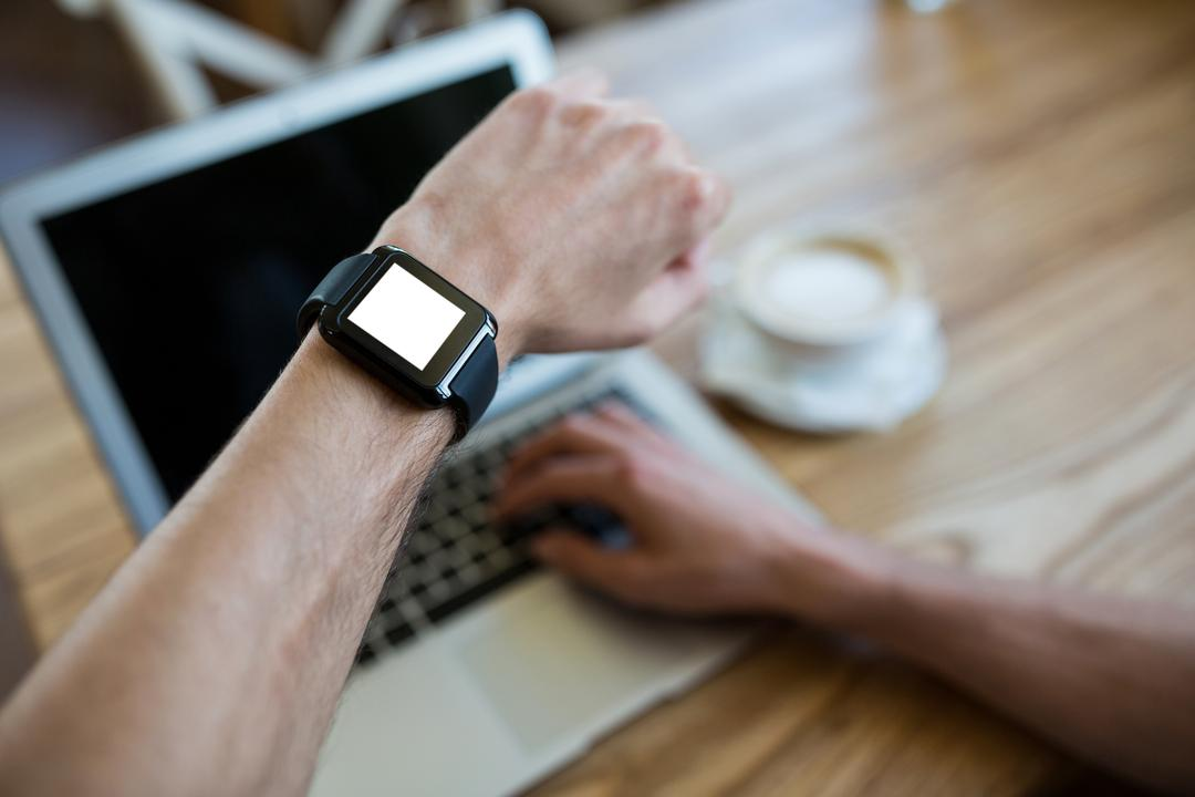 Close-up of hand wearing smartwatch using a laptop in coffee shop