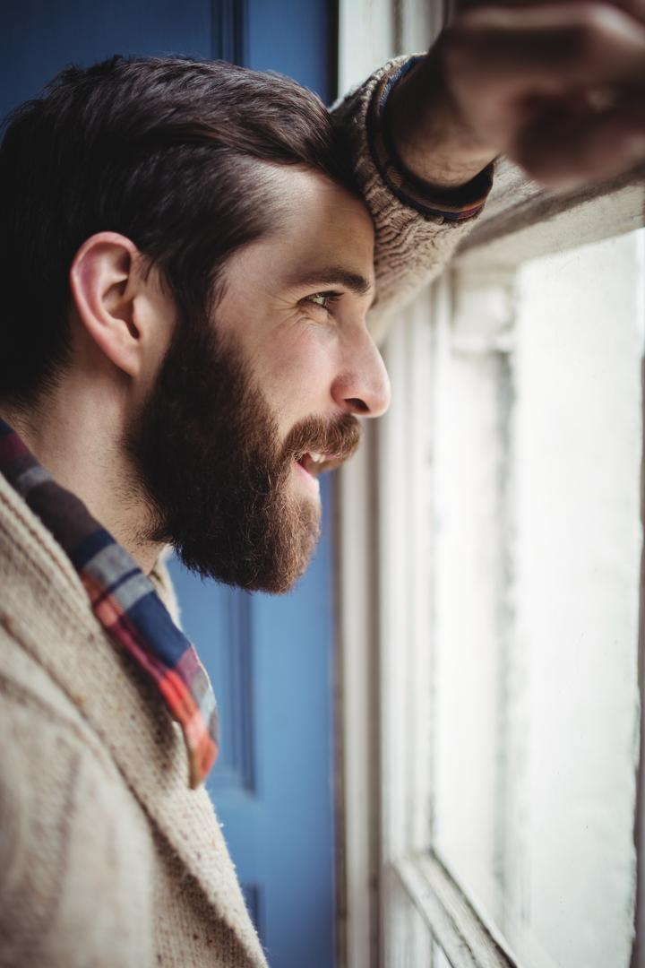 Man looking through window at home