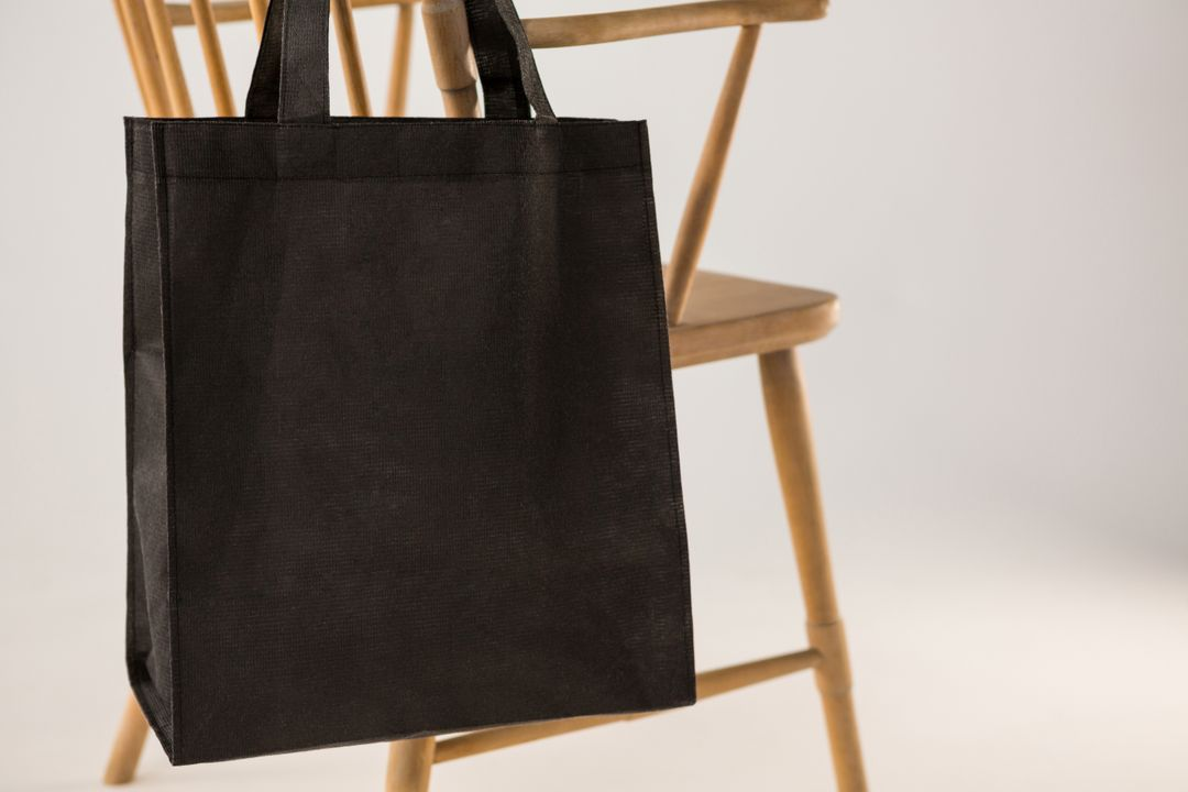 Black bag hanging on a wooden chair against white background