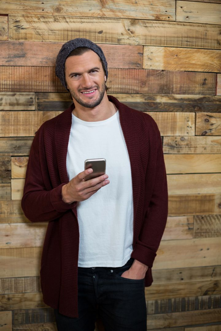 Portrait of man using mobile phone against wooden wall in café