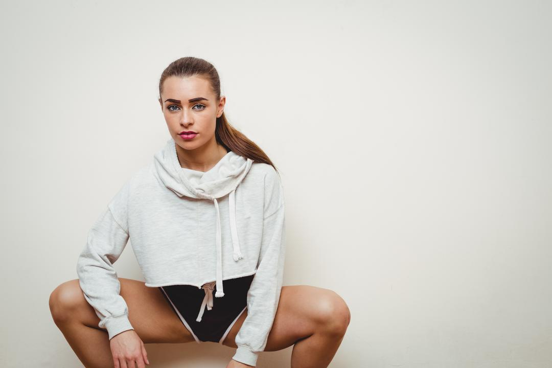 Portrait of a pretty woman crouching hip hop dance in studio Free Stock Images from PikWizard