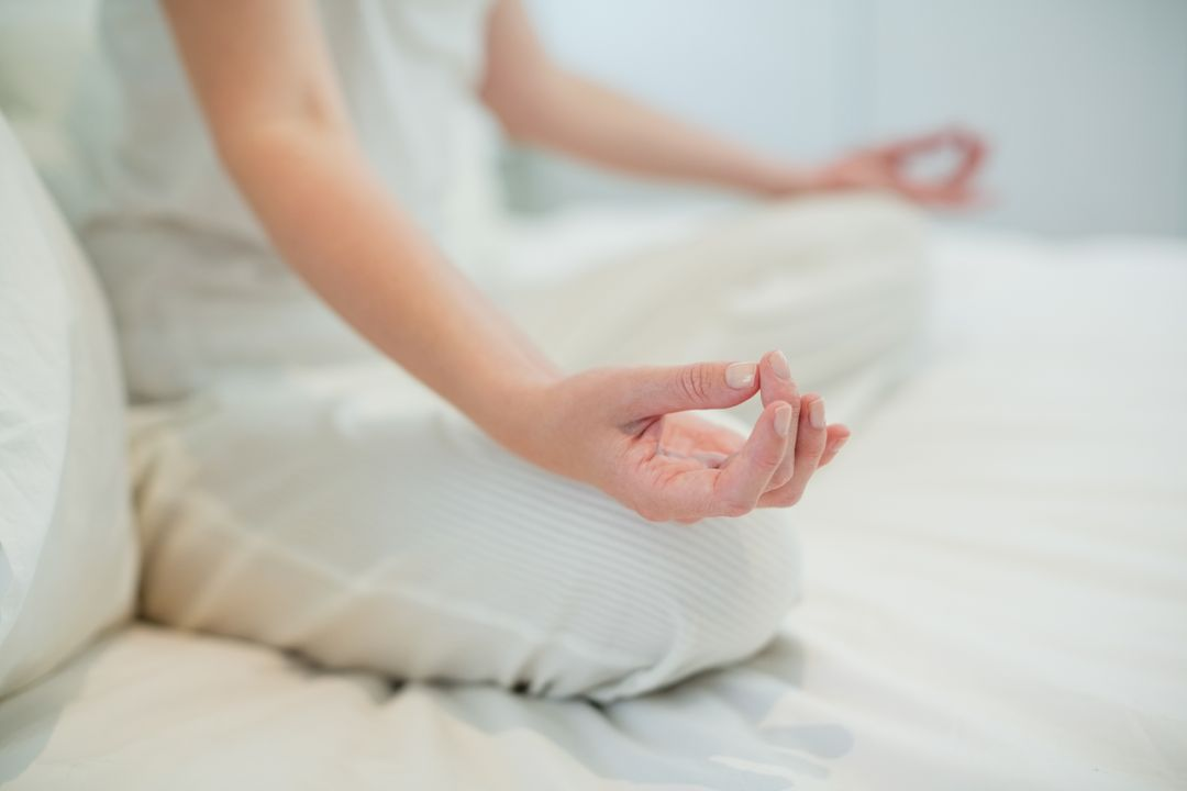Woman doing meditation on her bed relaxing