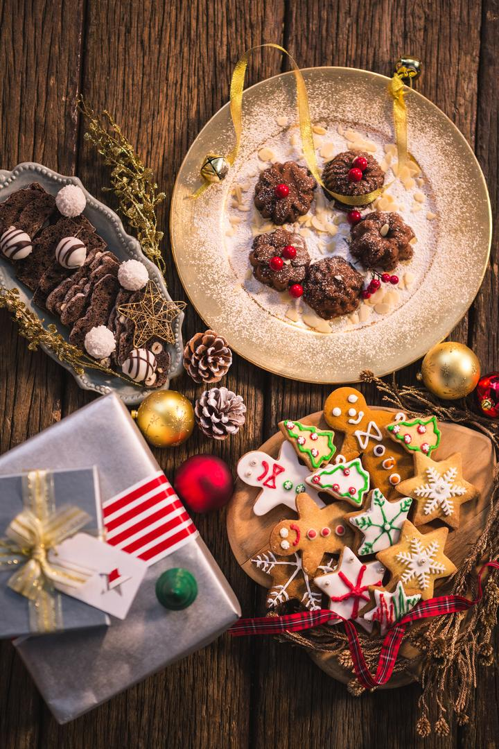 Close-up of various christmas desserts and gifts on wooden table Free Stock Images from PikWizard