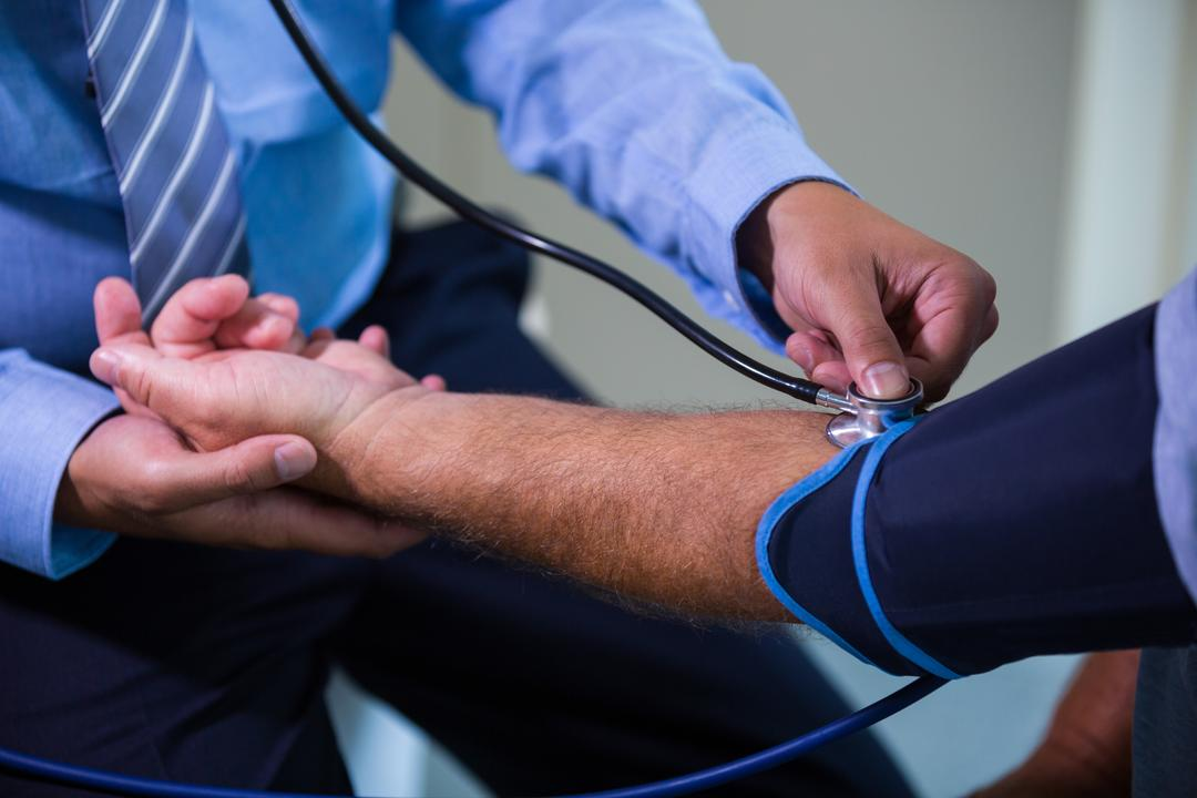 Male doctor checking blood pressure of patient at the hospital Free Stock Images from PikWizard