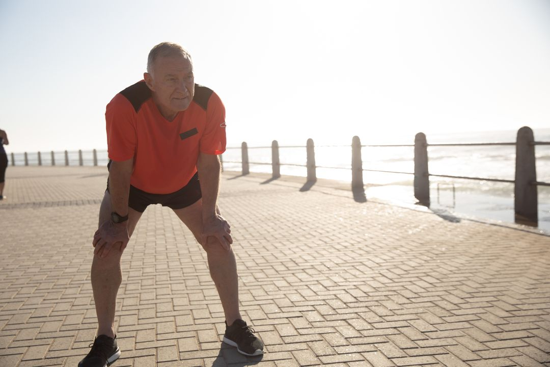 Senior Caucasian man working out on promenade by the sea wearing sports clothes, resting during workout. Retirement healthy lifestyle activity. Free Stock Images from PikWizard