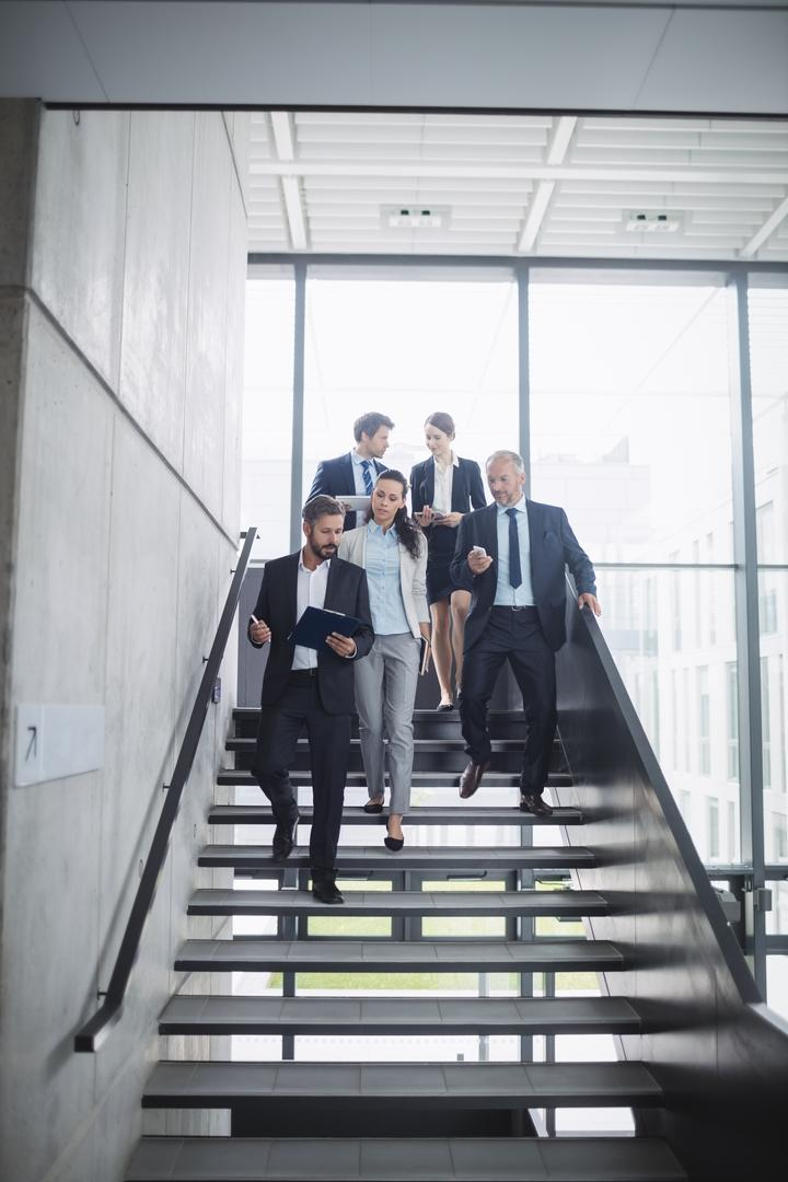 Confident businesspeople standing on staircase in office