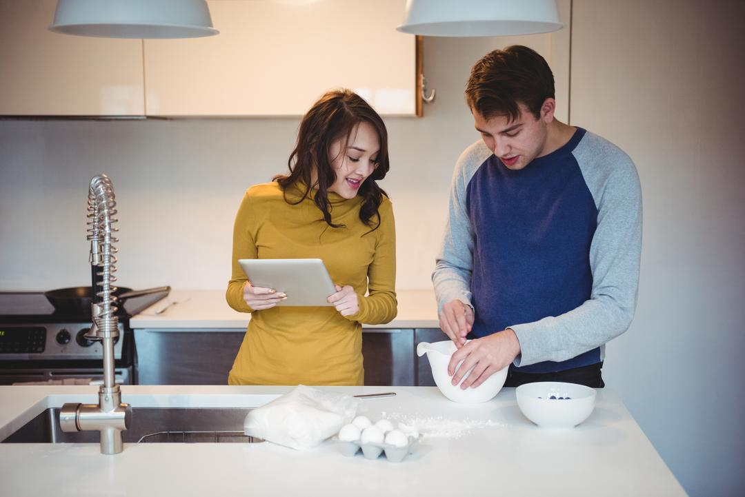 Couple using digital tablet while preparing cookies in kitchen at home