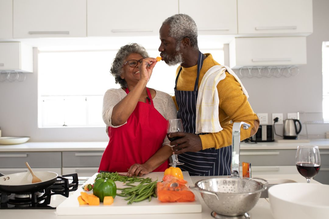 A senior African American couple at home together, social distancing and self isolation in quarantine lockdown during coronavirus covid 19 epidemic, woman feeding man in kitchen. Free Stock Images from PikWizard